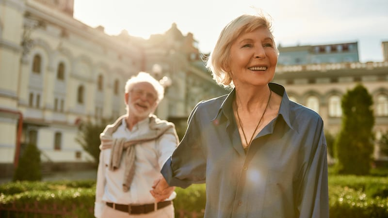 Beautiful and happy senior couple holding hands and smiling