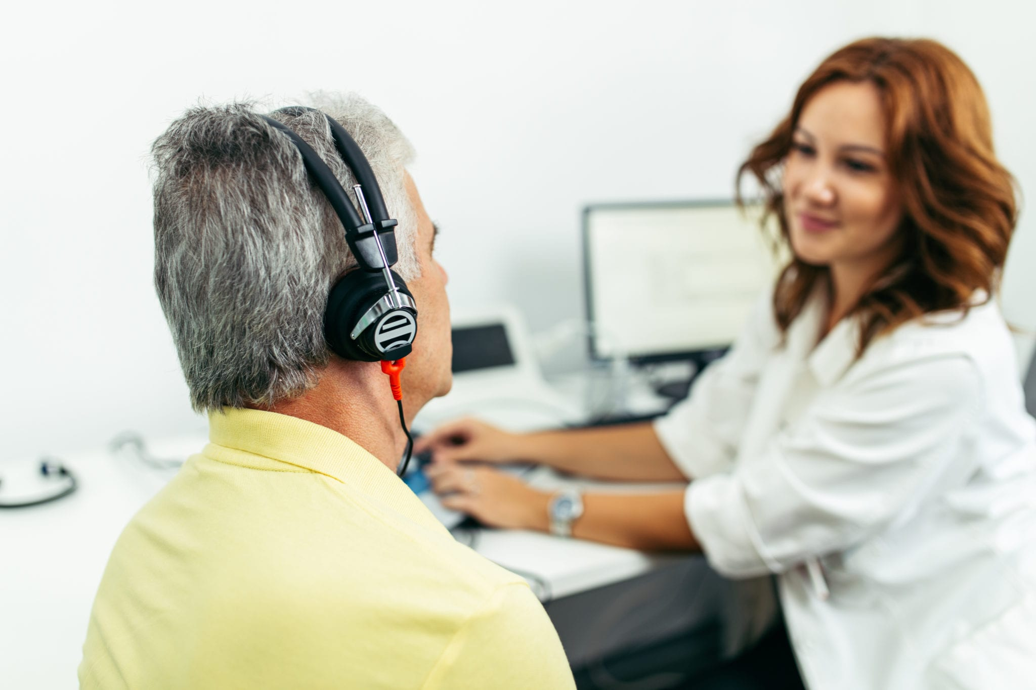 Why should you see a doctor of audiology for a hearing aid fitting?