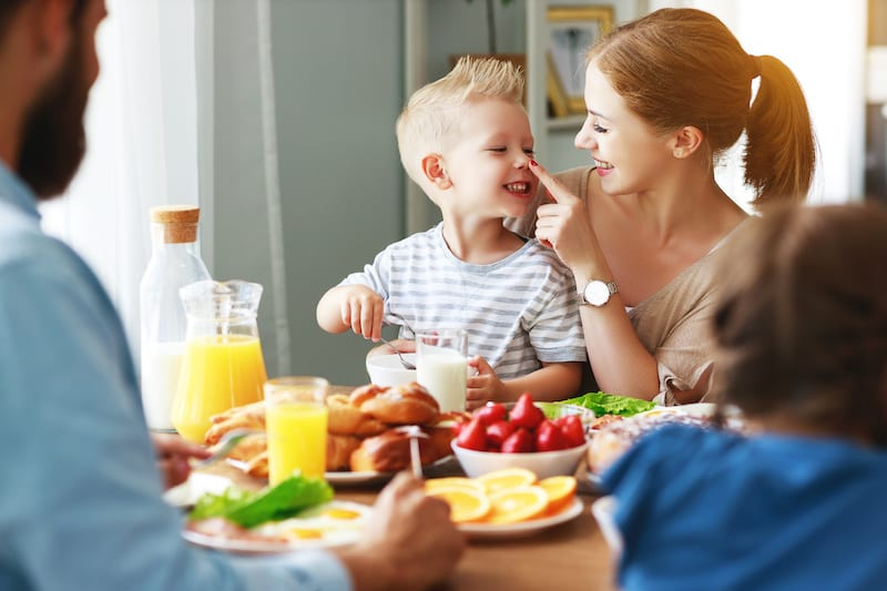family mother father and children have Breakfast in kitchen in morning
